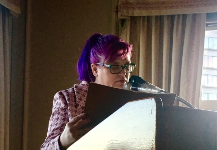 Woman reading poetry at lectern before a microphone in sunlit room.
