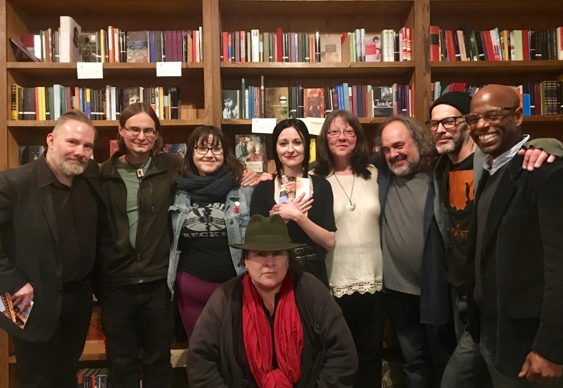 close group of people smiling standing before a bookshelf in a book store